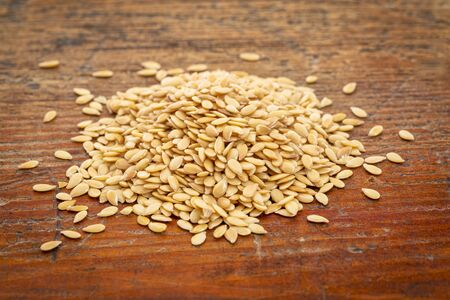 pile of gold flax seeds  against a grunge wood background