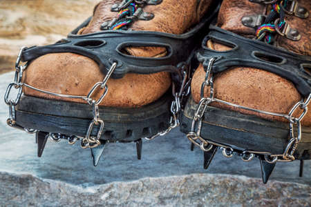 crampons: old hiking boots with trail crampons on stone background