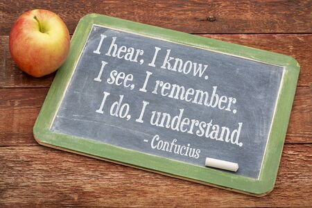 remember: I hear, I know. I see I remember. I do, I understand. - Confucius quote  on a slate blackboard against red barn wood