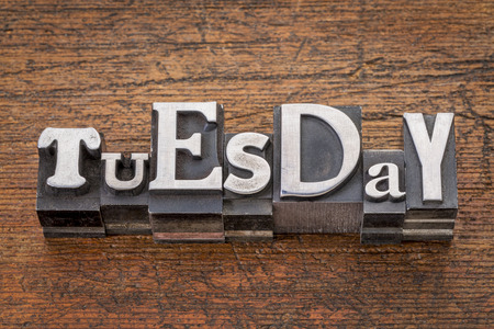 Tuesday word in mixed vintage metal type printing blocks over grunge wood photo