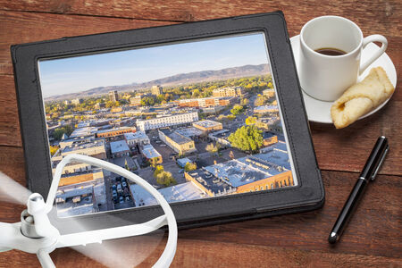 fort collins: drone aerial photography concept - reviewing aerial pictures of Fort Collins downtown on a digital tablet with a drone rotor and cup of coffee