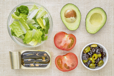romaine: top view of sardine salad ingredients - romaine lettuce, tomato, olives, avocado and canned sardines