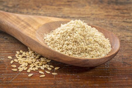gold flax: gold flax meal on a wooden spoon with seeds against a grunge wood