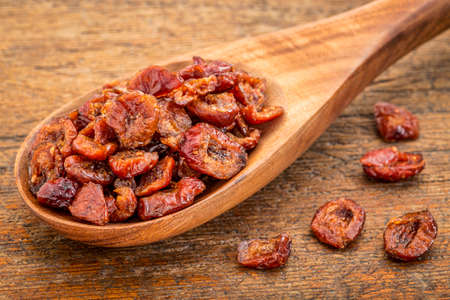 dried cranberry fruit on a wooden spoon against grunge wood background