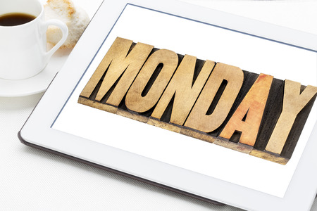 wood type: Monday - a word in letterpress wood type on digital tablet with a cup of coffee.
