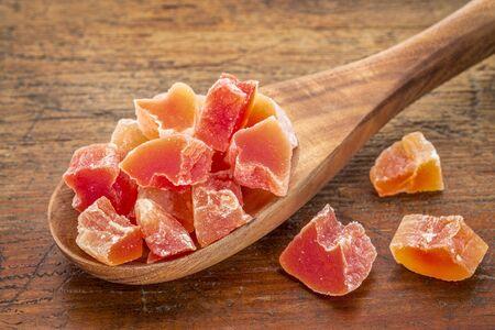 papaya: chunks of dried papaya fruit on a wooden spoon against grunge wood background