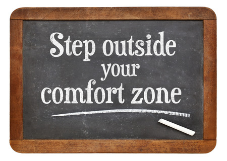 step outside your comfort zone - motivational advice on a vintage slate blackboard