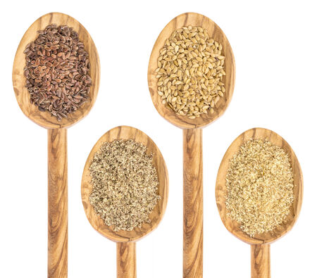 flax: gold and brown flax seed and meal - isolated collection of wooden spoons Stock Photo