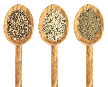 hemp seed, hearts and protein powder on isolated wooden spoons