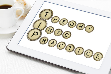 explained: TIP (theory into practice) acronym explained with old typewriter keys on a digital tablet with a cup of coffee Stock Photo