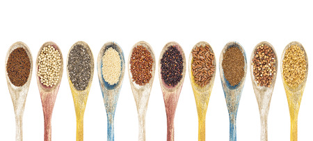 red quinoa: a collection of gluten free grains and seeds on isolated wooden spoons - kaniwa, sorghum, chia, amaranth,red quinoa, black quinoa, brown rice, teff, buckwheat, gold flax (from left to right) Stock Photo
