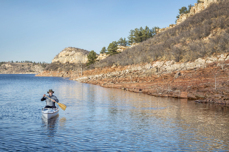 horsetooth reservoir: senior male paddling a decked expedition canoe on a mountain lake - Horsetooth Reservoir near Fort Collins, Colorado, early spring scenery Stock Photo