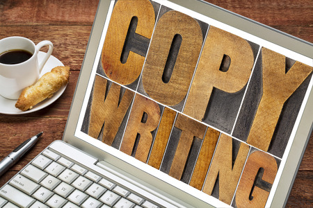 copywriting: copywriting word in letterpress wood type printing blocks on a laptop with cup of coffee