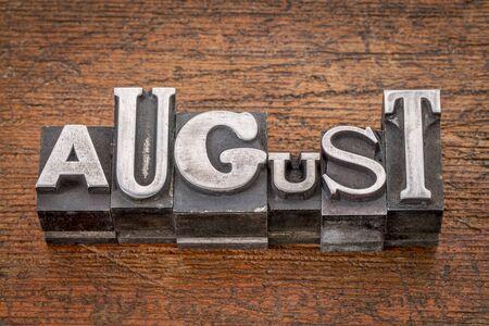 August  word in mixed vintage metal type printing blocks over grunge wood photo