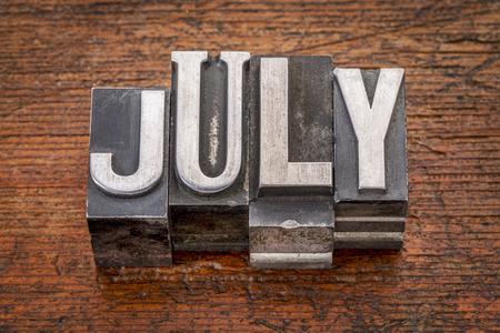 July word in mixed vintage metal type printing blocks over grunge wood photo