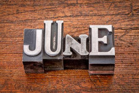 June word in mixed vintage metal type printing blocks over grunge wood photo