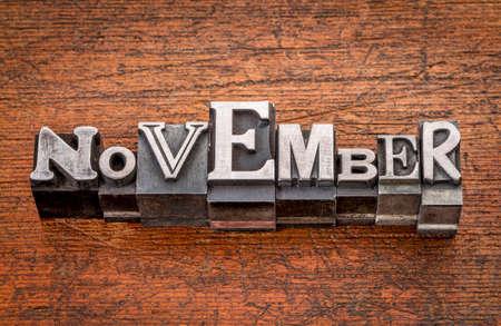 November word in mixed vintage metal type printing blocks over grunge wood photo