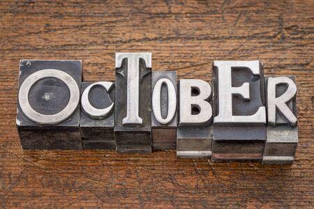 October word in mixed vintage metal type printing blocks over grunge wood photo