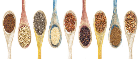 red quinoa: a collection of gluten free grains and seeds on isolated wooden spoons - kaniwa, sorghum, chia, amaranth,red quinoa, black quinoa, brown rice, teff, buckwheat  (from left to right) Stock Photo