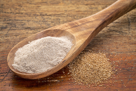 teff grain and flour i- a wooden spoon against grained wood background Banco de Imagens