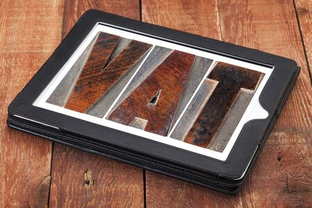 VAT (value added tax) - text in letterpress wood type printing blocks on a digital tablet photo
