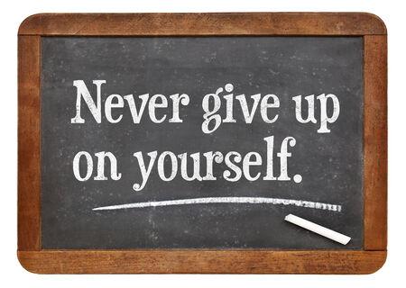 yourself: Never give up on yourself - motivational advice on a vintage slate blackboard Stock Photo