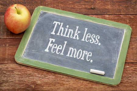 by feel: Think less. Feel more.  Motivational words on a slate blackboard against red barn wood Stock Photo