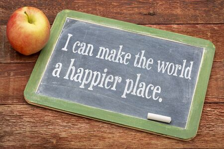 happier: I can make the world a happier place - positive words on a slate blackboard against red barn wood