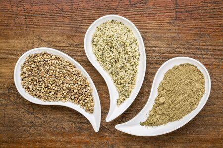 teardrop: hemp seeds, hearts and protein powder in teardrop shaped bowls against grunge wood