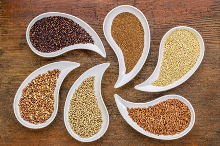set free: gluten free grain abstract - top view of teardrop shaped bowls with quinoa, teff, millet, rice, sorghum and buckwheat grains against grunge wood