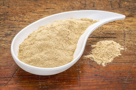 adaptogen: maca root powder in a teardrop shaped bowl against grunge wood Stock Photo