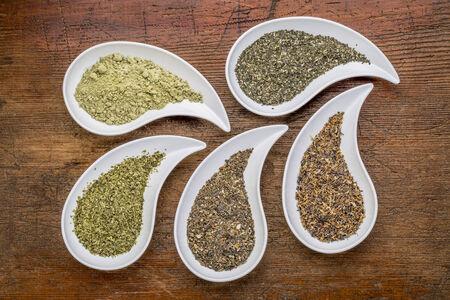 teardrop: teardrop shaped bowls of seaweed diet supplements (bladderwrack, sea lettuce, kelp, wakame and Irish moss) on a grunge wood background