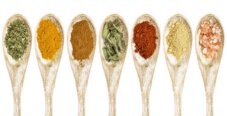 healthy seasoning and spices - a collection of isolated wooded spoons
