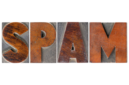 unsolicited: spam  word (unsolicited and unwanted commercial email messages) in isolated vintage wooden letterpress type blocks