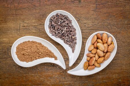 cacao beans, nibs and powder - top view of teardrop shaped bowls against rustic wood Stock Photo