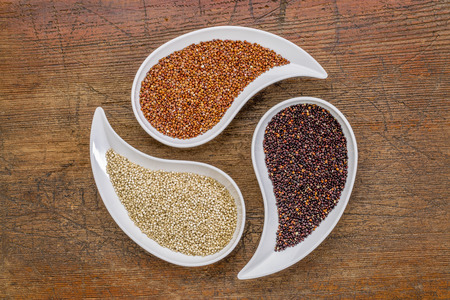 quinoa: white, red and black quinoa grain - top view of teardrop bowls against rustic wood