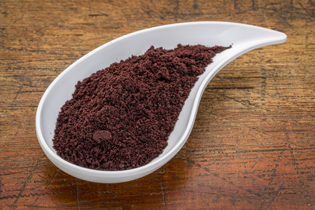 berry: dried acai berry powder in a teardrop shaped bowl against rustic wood