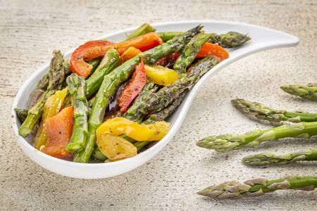 teardrop: roasted asparagus salad on a teardrop shaped bowl against white painted rustic wood with fresh asparagus Stock Photo