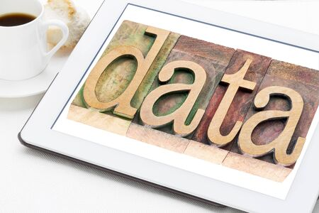 information age: information age concept - data word in letterpress wood type on a digital tablet with a cup of coffee