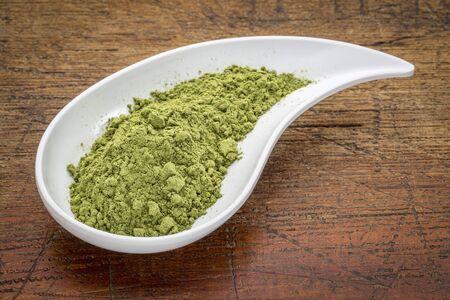 teardrop: moringa leaf powder in a teardrop shaped bowl against rustic wood