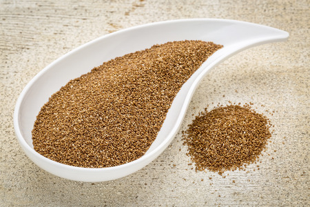 teardrop: gluten free teff grain on a teardrop shaped bowl against white painted grunge wood