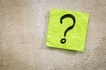 uncertainty or doubt concept - a question mark on a sticky note against rustic brand wood