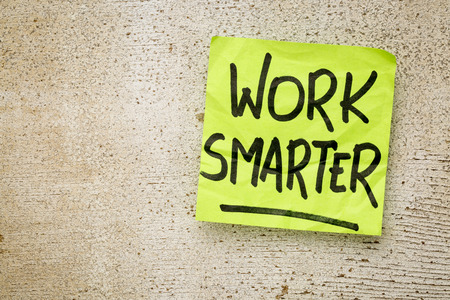 work smarter reminder on a green sticky note against rustic barn wood p productivity concept