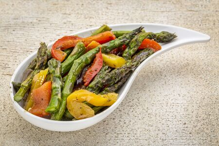 bell shaped: roasted asparagus salad with bell pepper on a teardrop shaped bowl against white painted rustic wood
