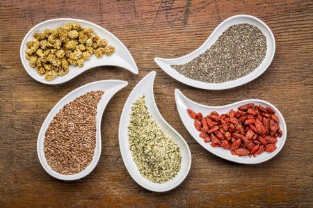 flax: superfood samples  (mulberry, chia seeds, hemp seeds, goji berry, flax seed) in teardrop shaped bowls against grunge wood