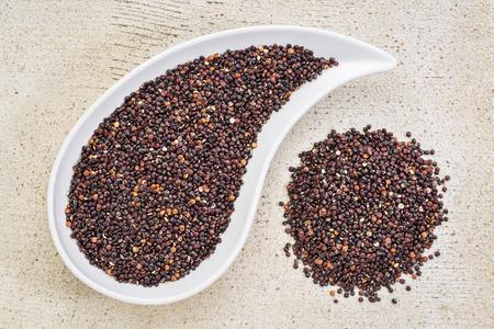 teardrop: gluten free black quinoa grain grown iin Bolivia ,  a teardrop shaped bowl against white painted grunge wood, top view