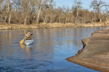 paddler: senior paddler in a decked expedition canoe on the South Platte River in eastern Colorado, winter scenery without snow