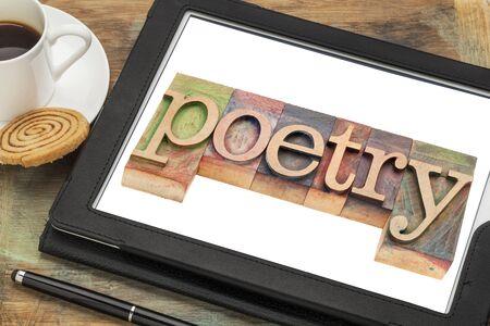 poëzie woord typografie - tekst in boekdruk hout op een digitale tablet met een kopje koffie Stockfoto