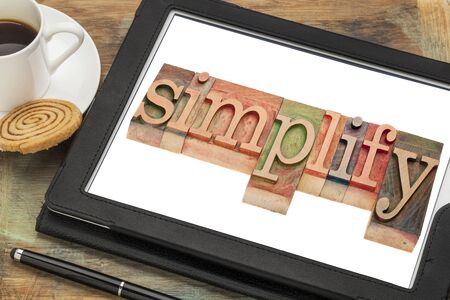simplify: simplify word typography - text in letterpress wood type on a digital tablet with a cup of coffee Stock Photo