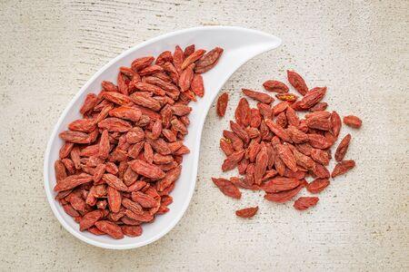 teardrop: dried goji berries in a teardrop shaped bowl against rustic white painted wood